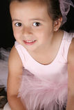Ballet girl. Cute little ballet girl wearing a tutu looking up at the camera Stock Photos