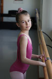Ballet girl standing next to the barre. A young ballet girl getting ready for her warm up on the barre Royalty Free Stock Photography