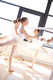 Ballet Girls in Reverse Leg Lift Holding a Bar Royalty Free Stock Photography
