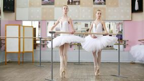 In the ballet hall, two girls in white ballet tutu, packs are engaged at ballet, rehearse pas de bourre, Young. Ballerinas standing on toes in pointe shoes at stock video footage