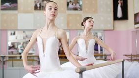 In the ballet hall, two girls in white ballet tutu, packs are engaged at the ballet, rehearse turning, Young ballerinas. Standing at railing in ballet hall stock footage