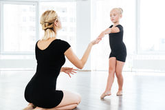 Ballet instructor directing little cute ballerina during dance practice Stock Image