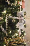 Ballet Kitty Cat Ornament Hanging from Christmas Tree. A gray, ballet kitty cat ornament hanging from the Christmas tree with lights and garland royalty free stock images
