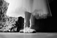 Ballet. Legs of a ballerina in pointe shoes before going on stage Stock Image