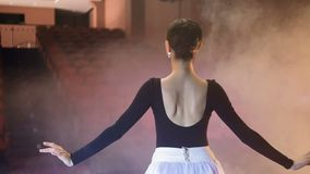 A ballerina, ballet performer looks to the empty seats and dances. stock video