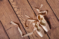 Ballet pointe shoes lie on wooden floor. Stock Photography