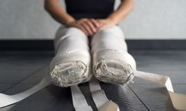 Ballet pointe shoes on a young female ballerina untied in ballet class royalty free stock photo
