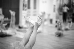 Ballet position of small ballerina's feet. Young ballerinas training, low section; monochrome stock photo