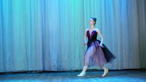 Ballet rehearsal, on the stage of the old theater hall. Young ballerina in lilac black dress and pointe shoes, dances. Elegantly certain ballet motion, grand stock video