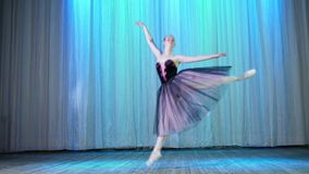 Ballet rehearsal, on the stage of the old theater hall. Young ballerina in lilac black elegant dress and pointe shoes. Dances elegantly certain ballet motion stock footage