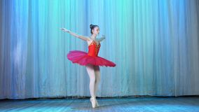 Ballet rehearsal, on the stage of the old theater hall. Young ballerina in red ballet tutu and pointe shoes, dances stock video