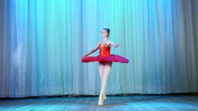 Ballet rehearsal, on the stage of the old theater hall. Young ballerina in red ballet tutu and pointe shoes, dances