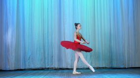Ballet rehearsal, on the stage of the old theater hall. Young ballerina in red ballet tutu and pointe shoes, dances. Elegantly certain ballet motion, tour stock footage