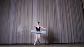 Ballet rehearsal, on the stage of the old theater hall. Young ballerina in white ballet tutu and pointe shoes, dances. Elegantly certain ballet motion, glissad stock video footage