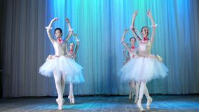 Ballet rehearsal, on the stage of the old theater hall. Young ballerinas in elegant dresses and pointe shoes, dance
