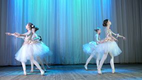 Ballet rehearsal, on the stage of the old theater hall. Young ballerinas in elegant dresses and pointe shoes, dance. Elegantly certain ballet motions, pass stock video footage