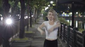 Ballet rubio del baile de la muchacha en la calle en la noche que expresa tolerancia y elegancia almacen de metraje de vídeo
