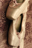 BALLET SHOES. A pair of ballet shoes against satin & lace Royalty Free Stock Photos