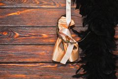 Ballet shoes and boa hanging. Pair of new ballet dancing shoes with hard insoles hand nearby black feather boa on the wooden background. Ready to dancing show Stock Photo
