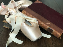 Ballet shoes and books. Ballet shoes resting on vintage books.  Wooden floor and blurred background Stock Photography