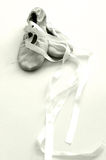 Ballet shoes, hight key sepia. A pair of soft leather ballet shoes for little girls, with long satin ribbons for tying. Taken with clean composition and royalty free stock images