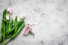 Ballet shoes near delicate flowers on grey background top view copy space. Ballet shoes near delicate flowers on grey background top view stock photography