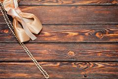 Ballet shoes and a necklace. Pair of classic silk ballet shoes with hard insole - pointe - and a pearl necklace lie on wooden background. Ready to show concept Royalty Free Stock Images