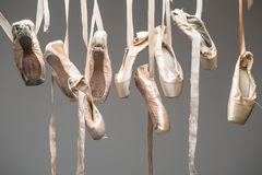 Ballet shoes pointe isolated. Many pairs of ballet shoes hang haphazardly on a hanger. Pointe in different condition from new to very shabby old. Horizontal royalty free stock photo