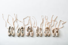 Ballet shoes pointe isolated. Many pairs of ballet shoes in pairs stand in a row. Pointe shoes in different condition from new to very shabby old. Tapes are stock image