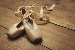 Ballet Shoes on Wooden Floor. Two ballet shoes on wooden floor royalty free stock photography