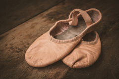 Ballet shoes on wooden floor. Royalty Free Stock Images