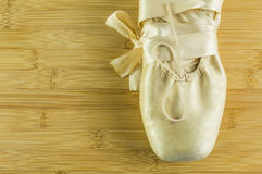 Ballet shoes on wooden flor. Detail of a ballet shoes on a wooden background Royalty Free Stock Image
