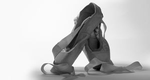 Ballet slippers 1. Very worn and loved pair of ballet point shoes, black and white on white background Stock Photo