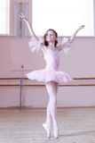 Ballet studio. Petite ballerina posing at camera Royalty Free Stock Photo