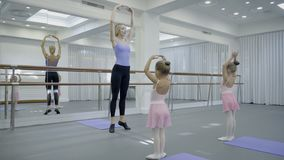 In ballet studio teacher shows children dancing movements near mirror. Young and beautiful woman teaches two little girls in skirts right positions during stock video footage