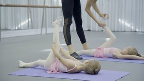 In ballet studio teacher trains socks on feet of children in shoes. Two little girls lie on mats and coach shows right positions for development of foot stock video footage