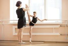 Ballet teacher adjusting leg position of young ballerinas Stock Photos