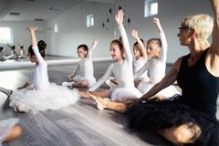 Ballet teacher and group of children ballerinas exercising in ballet studio. Ballet teacher and group of children ballerinas exercising in ballet school royalty free stock image