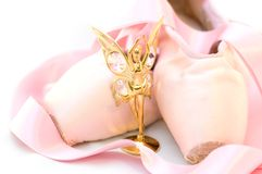Ballet theme. Little golden ballet dancer sculpture and a pair of rose pointes isolated on white Stock Images