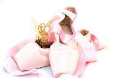 Ballet theme. Pair of pointes and small golden figurine isolated on white Stock Photos