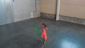 Ballet training indoors. Young woman ballerina dancing and performing circus numbers holding a strip. Mid shot stock video