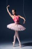 Balletdanser als marionet die over grijze achtergrond dansen Royalty-vrije Stock Foto's