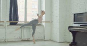 Balletdansers die developpe bij staaf praktizeren stock video
