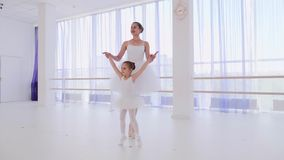 Balletleraar met meisje opleidingsstappen op tiptoe in de handen van de pointesgreep stock video