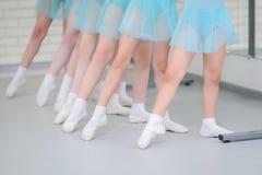 Balletschool De meisjesstudenten die dichtbij staaf praktizeren werken voor voetenposities Close-updetail van voeten binnen wordt royalty-vrije stock afbeelding