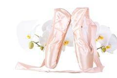 Ballett pointes mit Orchideen auf getrenntem Weiß stockfoto