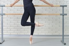 Balletto di pratica della ballerina allo studio di ballo vicino alla sbarra Fotografia Stock