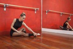 Balletto di pratica della donna sul pavimento di legno duro Fotografie Stock