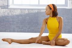 Balletttänzer, der auf Fußboden ausdehnt Lizenzfreie Stockfotografie