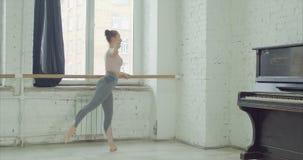Balletttänzer, die degage Übung am Barre üben stock footage
